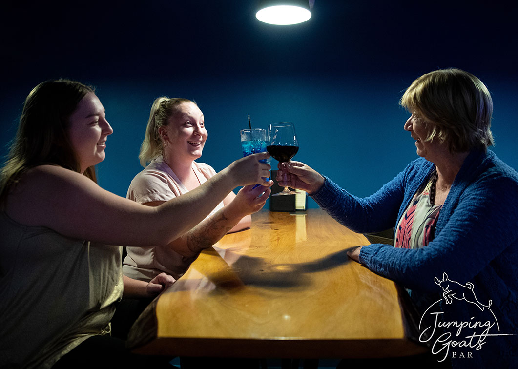 Three friends toasting with wine and cocktails over a timber slab table